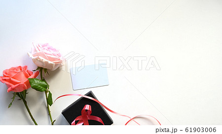 Top view copy space of pink and white rose close to black present box . 61903006