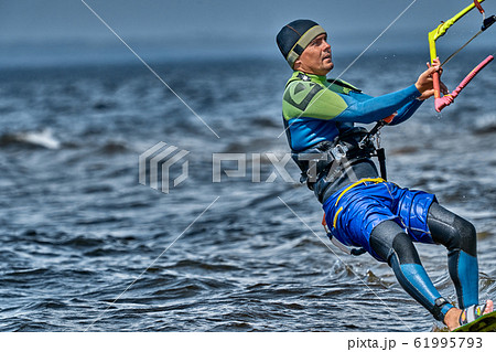 A male kiter slides on the surface of the water. 61995793