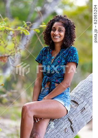 ヤシの木に座る笑顔の素敵な若い女性 62065204