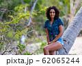 ヤシの木に座る素敵な若いアフリカ系女性 62065244