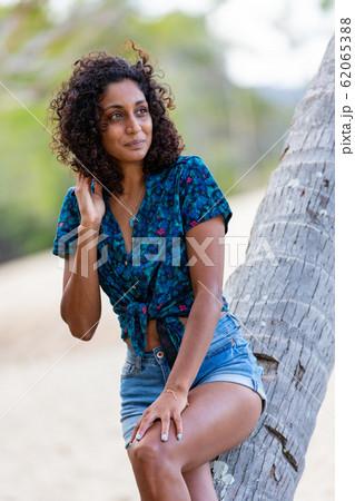 ヤシの木に座る素敵な若い女性 62065388