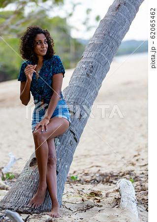 ヤシの木に座る素敵な若い女性 62065462