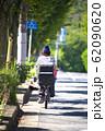 チャイルドシートを取り付けた自転車に乗る女性の後ろ姿 62090620
