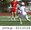 Boys playing in high school lacrosse game 62114128