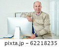 Businessman sitting on his desk 62218235
