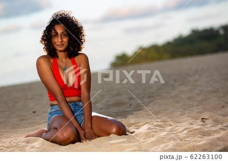夕方のビーチに座る浅黒い肌の彼女 62263100