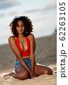 夕方のビーチに座る浅黒い肌の彼女 62263105