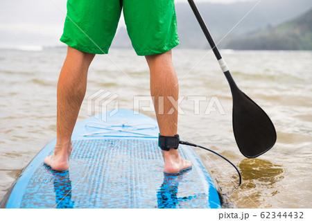 Paddleboard man paddling on SUP stand up paddle board on lake. Closeup of feet and legs 62344432