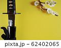 黄色い背景に少し抜いた日本刀と白い花が咲いた梅の枝 62402065