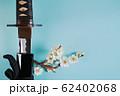 青い背景に少し抜いた日本刀と白い花が咲いた梅の枝 62402068