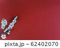 赤い背景に白い花が咲いた梅の枝と広いコピースペース 62402070