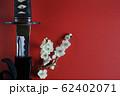 赤い背景に少し抜いた日本刀と白い花が咲いた梅の枝 62402071