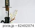 白い背景に少し抜いた日本刀と白い花が咲いた梅の枝 62402074