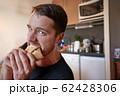 Man biting a sandwich 62428306