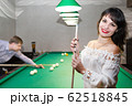 Man and woman play billiards. 62518845