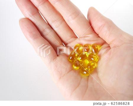 黄色いビタミン剤と手 62586828
