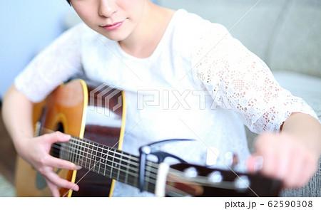 アコースティックギターを練習する女性イメージ 62590308