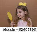 Portrait of emotional little girl with crown a yellow paper holding a mirror. handmade. cardboard background 62609395