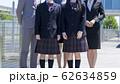 学校をバックに並ぶ講師と女子高校生のイメージカット 62634859