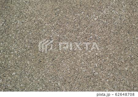 砂色でザラザラした細かい砂利が浮き出たコンクリート舗装の表面 62648708