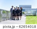 学校をバックに並ぶ講師と女子高校生 62654018