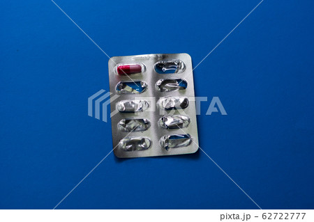 The last medicine pill on a blue background. 62722777