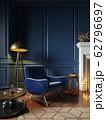 Classic royal blue color interior with armchair, fireplace, candle, floor lamp, carpet. 62796697