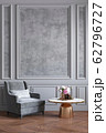 Classic gray interior with gray armchair, coffee table, flowers and wall moldings. 62796727