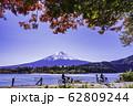 (山梨県)紅葉の河口湖・湖畔サイクリングを楽しむ人達と富士山 62809244