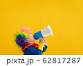 Funny kid clown playing against yellow background 62817287