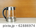 Glass stainless steel kettle on the marble and woody background 62886974
