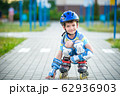 Smiling boy with inline skates and protective gear 62936903