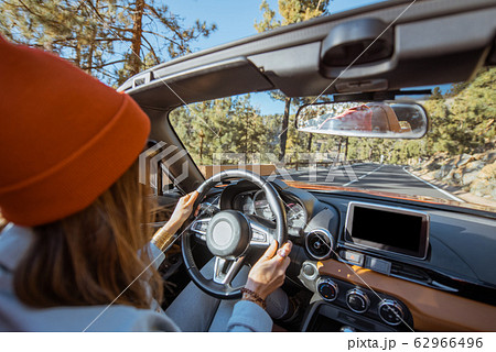 Woman driving a cabriolet on the mountain road 62966496