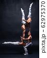 Four muscular man perform difficult acrobatic tricks on black studio  62975370
