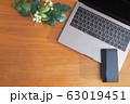 木目のデスクに置かれたノートパソコンとスマホと緑 63019451