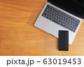 木目のデスクに置かれたノートパソコンとスマホ 63019453
