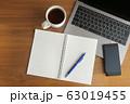 木目のデスクに置かれたノートパソコンとスマホとコーヒーとノート 63019455