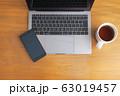 木目のデスクに置かれたノートパソコンとスマホとコーヒー 63019457