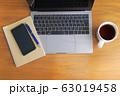 木目のデスクに置かれたノートパソコンとスマホとコーヒーとノート 63019458