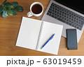 木目のデスクに置かれたノートパソコンとスマホとコーヒーとノートと緑 63019459