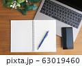 木目のデスクに置かれたノートパソコンとスマホとノートと緑 63019460