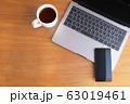 木目のデスクに置かれたノートパソコンとスマホとコーヒー 63019461