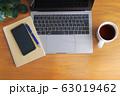 木目のデスクに置かれたノートパソコンとスマホとコーヒーとノートと緑 63019462