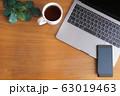 木目のデスクに置かれたノートパソコンとスマホとコーヒーと緑 63019463