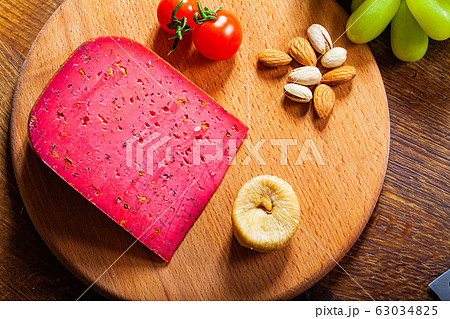 Chunk of red cheese on wooden background. 63034825