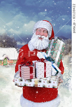 雪景色の中、クリスマスプレゼントを抱えて家の前にいる笑顔のサンタクロース 63139422