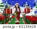 雪景色の中、雪だるまの前をクリスマスのコスチュームを着てプレゼントの箱を両手に乗せて笑う日本人の若い 63139426