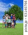 公園の大きな木の前に立つ笑顔のファミリー 63140766