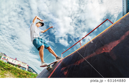 Portrait of a young skateboarder doing a trick on his skateboard on a halfpipe ramp in a skate park in the summer on a sunny day. The concept of youth culture of leisure and sports 63164880