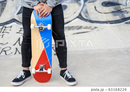 Close up of unrecognizable young man holding longboard or skateboard in the park. 63168226